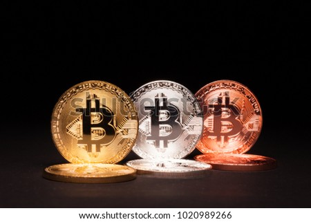 Silver copper and gold Bitcoin on black background in focus