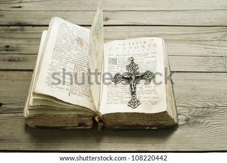 silver cross and old holy bible, wooden background