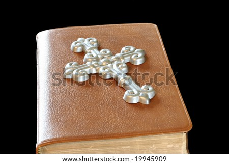 Silver cross on a brown leather bible - stock photo
