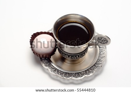 Silver cup of coffee with white cake is on the white background