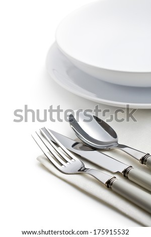 silver cutlery and plates on white background