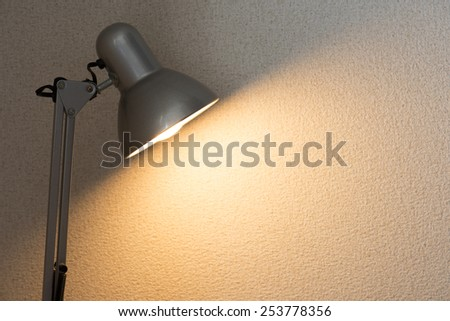 Silver desk lamp or arm lamp in front of a white wall with incandescent type light bulb illuminating the wall.   - stock photo