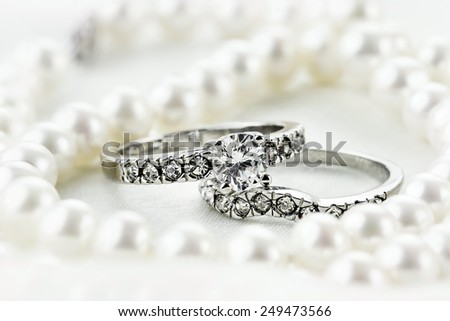 Silver diamond engagement ring and wedding band lying inside of a beautiful pearl necklace. Extreme shallow depth of field with selective focus on rings. - stock photo