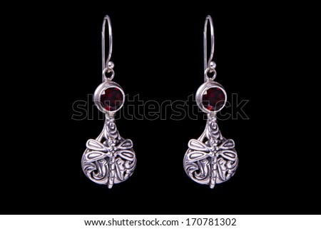 Silver earrings on a black background - stock photo