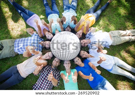 Silver earth against happy friends in the park lying in circle - stock photo