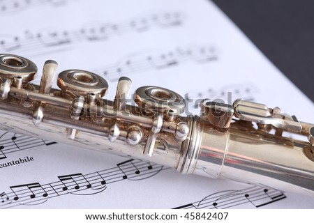 Silver flute superimposed on flute sheet music featuring a classical score - stock photo