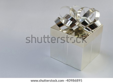 silver gift box with bow, isolated on neutral background with copy space at left - stock photo