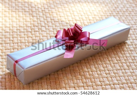 Silver gift box with pink bow on woven straw background - stock photo