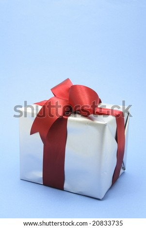 Silver Gift Box with Red Ribbons on Blue Background