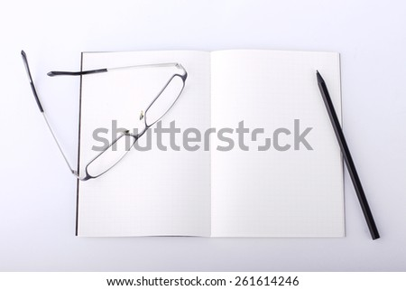 silver glasses and black pencil on open book with isolated background - stock photo