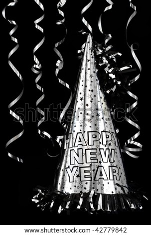 Silver Happy New Year party hat isolated on black with silver streamers. - stock photo