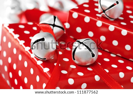 Silver jingle bells with red satin ribbon on gifts wrapped in fun polka dot paper.  Macro with shallow dof. - stock photo