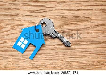 Silver key with blue house figure on wooden background - stock photo