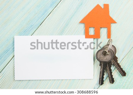 Silver key with house figure and blank business card on wooden background. Real Estate Concept. Top view. - stock photo