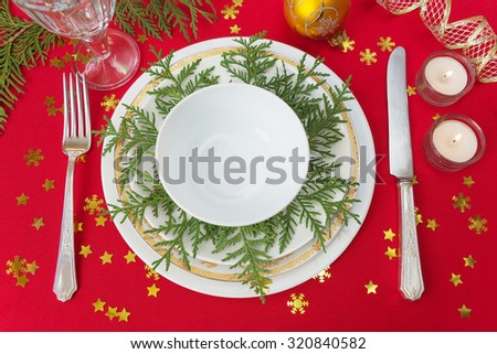 Silver knife, fork, dinner plates, wineglass and burning candles, which is located on a table covered with a red tablecloth strewn with golden confetti in the shape of snowflakes - stock photo