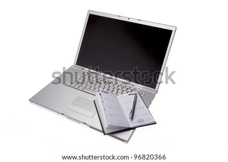 Silver lap top with opened pocket planner and silver pen on a white background - stock photo