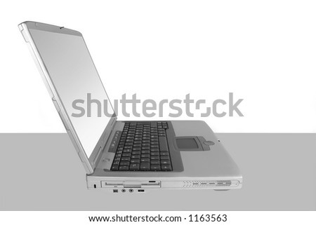 Silver laptop with a white and silver screen set against a white and grey background - stock photo