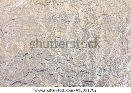 Silver metal aluminum background - Rippled aluminium foil view from above - Dark colors and shadows down  to emphasize the metallic material - stock photo