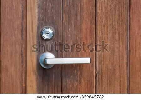 Silver metal door handle and brown wood door - stock photo
