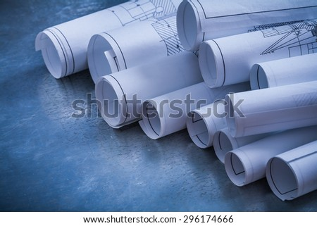 Silver-metal surface with variety of rolled construction plans close-up image building and architecture concept. - stock photo