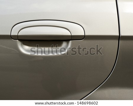 Silver metallic car's door fragment with a handle - stock photo