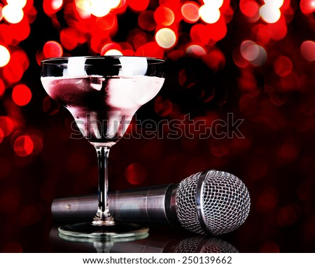 Silver microphone and cocktail on table on red lights background - stock photo
