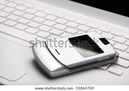 Silver mobile phone on a white laptop. Top view. Selective focus on a phone.