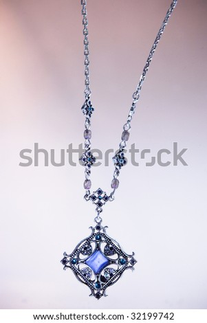 Silver necklace with blue gem - stock photo
