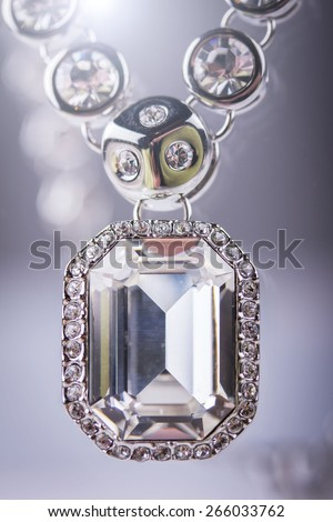 Silver necklace with diamond. Isolated on grey. Lens flare - stock photo