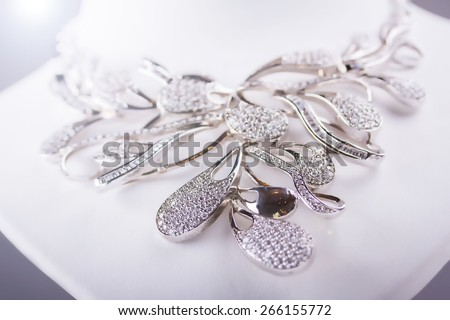 Silver necklace with little diamonds. Isolated on grey. Lens flare. Small depth of field - stock photo
