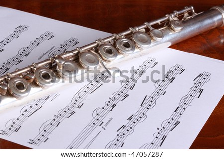 Silver open key flute and classical sheet music resting on a polished wood surface - stock photo