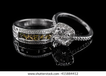 Silver or white gold engagement rings with yellow gems and diamonds on black glass background