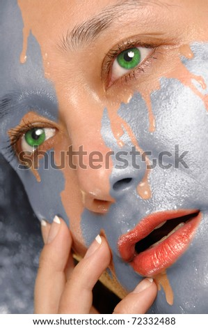 Silver paint washing out of  woman face revealing clean skin - stock photo