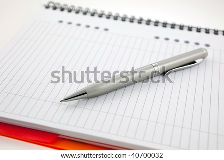 silver pen and paper orange notebook. small GRIP