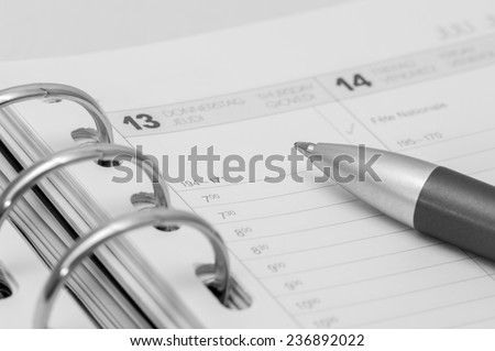 silver pen on open business agenda in black and white