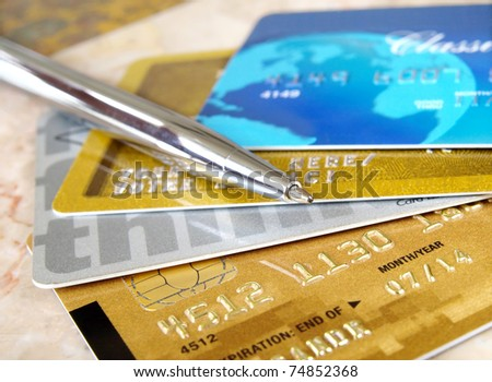 Silver pen on the pile of credit cards . - stock photo
