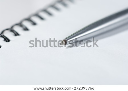 Silver pen on top of a notebook. - stock photo