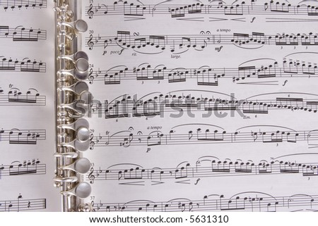 Silver Piccolo on sheet music - stock photo