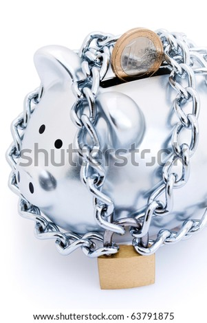 Silver piggy bank padlocked with chains and padlock with single Euro partially inserted in slot, on white background.
