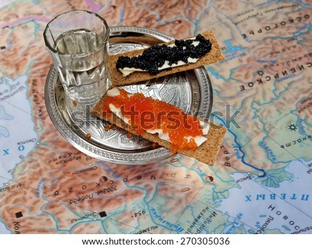 silver plate with black and red caviar and glass of vodka on a background of old maps of Siberia - stock photo