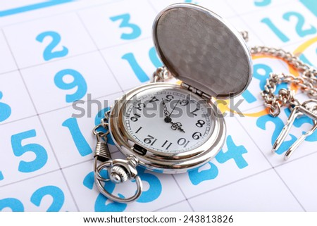 Silver pocket clock on calendar background - stock photo