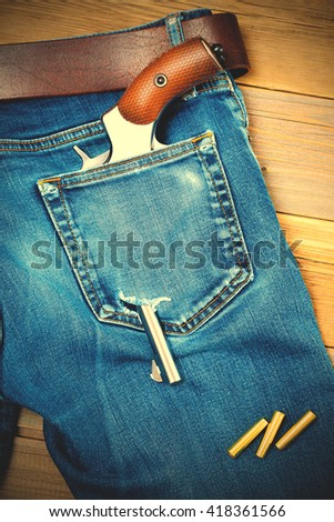 silver revolver in the back pocket of old blue jeans with a leather belt. instagram image filter retro style - stock photo