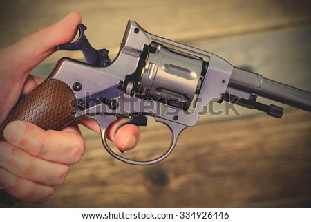 silver revolver Nagant in human hand. instagram image filter retro style - stock photo