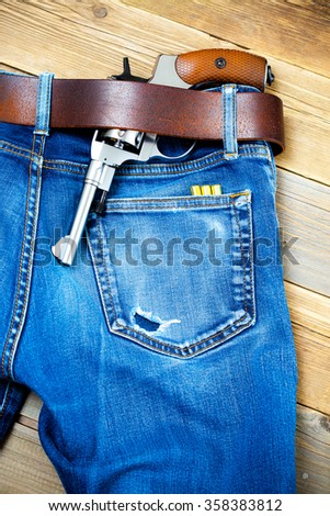silver revolver under a leather belt of blue jeans - stock photo