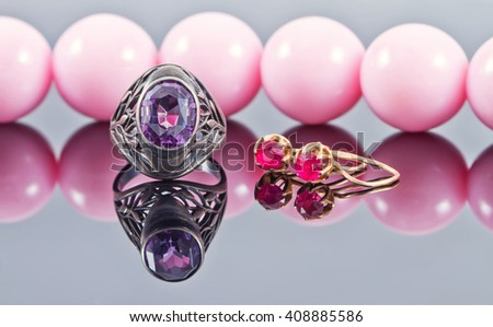 Silver ring with amethyst and gold earrings with a ruby on a background of pink beads - stock photo