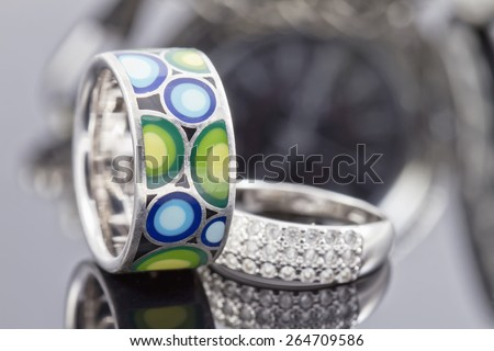 silver ring with precious stones and a ring with a colored ceramic enamel on the background of pocket watches - stock photo