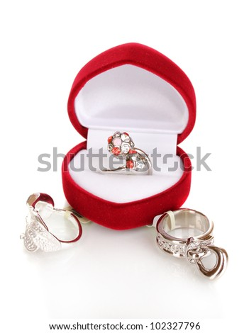 Silver ring with red, pink and clear crystals in red velvet box and some silver rings isolated on white