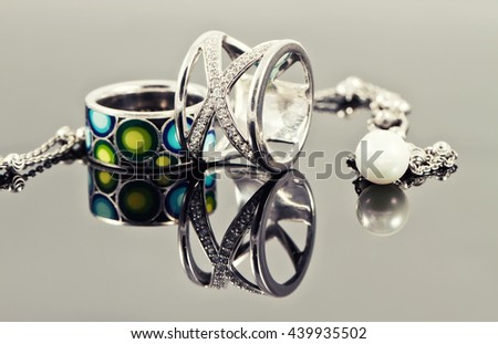 Silver rings of various shapes and chain necklace with pearls - stock photo