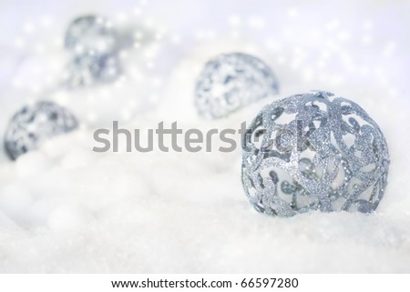 Silver rustical Christmas baubles in the snow. - stock photo
