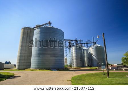Silver, shiny agricultural silos - stock photo